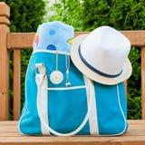 Μπλε τσάντα με την πετσέτα και καπέλο για το υπαίθριο Σαββατοκύριακο λιμνών ή παραλιών. Στοκ εικόνα με δικαίωμα ελεύθερης χρήσης