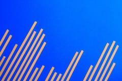Μπλε υπόβαθρο με τα κίτρινα μακριά ακατέργαστα ζυμαρικά Στοκ εικόνες με δικαίωμα ελεύθερης χρήσης