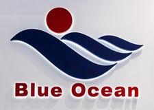 Μπλε ωκεάνιο λογότυπο επιχείρησης Πλαστικές μπλε επιστολές με τα φω'τα στον άσπρο τοίχο Στοκ Φωτογραφίες