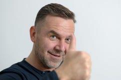 Μπλε eyed μέσης ηλικίας άτομο που παρουσιάζει αντίχειρα Στοκ φωτογραφία με δικαίωμα ελεύθερης χρήσης