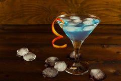 Μπλε Martini κοκτέιλ στο σκοτεινό ξύλινο υπόβαθρο Στοκ Φωτογραφίες