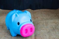 Μπλε piggy τράπεζα στο υπόβαθρο κάνναβης Στοκ Φωτογραφία