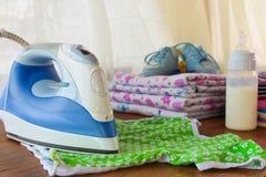 Μπλούζα των παιδιών κτυπημάτων σιδήρου Στο υπόβαθρο, πάνες, ενδύματα μωρών, ειρηνιστής, μικρά παπούτσια Στοκ εικόνα με δικαίωμα ελεύθερης χρήσης