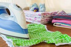 Μπλούζα των παιδιών κτυπημάτων σιδήρου Στο υπόβαθρο, τις πάνες, τα ενδύματα μωρών, τον ειρηνιστή, τα μικρά παπούτσια και ένα μπου Στοκ φωτογραφία με δικαίωμα ελεύθερης χρήσης