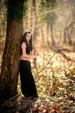 Μυθική γυναίκα πλασμάτων, που κρατά το ξίφος της από ένα δέντρο στο πρόσθιο μέρος Στοκ φωτογραφία με δικαίωμα ελεύθερης χρήσης