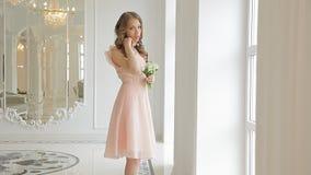 Μυθικό fiancee στο όμορφο μπεζ φόρεμα με μια ανθοδέσμη των κοιλάδα-κρίνων φιλμ μικρού μήκους