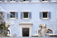 Μυθολογικά πλάσματα ως αγάλματα πηγών και χλωμός - μπλε σπίτι Στοκ εικόνες με δικαίωμα ελεύθερης χρήσης