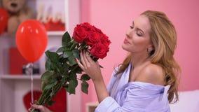 Μυρίζοντας δέσμη σαγηνευτικών γυναικών των κόκκινων τριαντάφυλλων, παράδοση ανθοδεσμών, ημέρα βαλεντίνων απόθεμα βίντεο