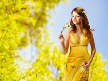 Μυρίζοντας λουλούδια γυναικών, πορτρέτο άνοιξη του όμορφου κοριτσιού στο yel Στοκ Εικόνες