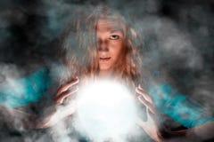 Μυστήρια γυναίκα που καθιστά μερικών μαγικών Στοκ φωτογραφία με δικαίωμα ελεύθερης χρήσης