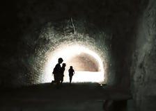 Μυστήρια εικόνα των παιδιών ghostlike σε μια σκοτεινή σπηλιά στοκ εικόνα