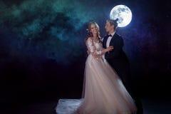 Μυστήρια και ρομαντική συνεδρίαση, η νύφη και ο νεόνυμφος κάτω από το φεγγάρι Αγκαλιάσματα από κοινού Μικτά μέσα Στοκ Φωτογραφία