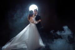 Μυστήρια και ρομαντική συνεδρίαση, η νύφη και ο νεόνυμφος κάτω από το φεγγάρι Αγκαλιάσματα από κοινού Μικτά μέσα Στοκ φωτογραφία με δικαίωμα ελεύθερης χρήσης