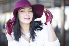 Μυστήρια νέα γυναίκα σε ένα burgundy καπέλο και τα γάντια Στοκ Φωτογραφίες