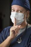 Μυστικοπαθής θηλυκός γιατρός με το δάχτυλο μπροστά από το στόμα Στοκ εικόνα με δικαίωμα ελεύθερης χρήσης