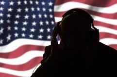 Μυστικός πράκτορας στα ακουστικά στο υπόβαθρο της αμερικανικής σημαίας στοκ φωτογραφία με δικαίωμα ελεύθερης χρήσης