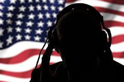 Μυστικός πράκτορας στα ακουστικά στο υπόβαθρο της αμερικανικής σημαίας στοκ φωτογραφίες με δικαίωμα ελεύθερης χρήσης
