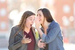 Μυστικό αφήγησης γυναικών κουτσομπολιού στον έκπληκτο φίλο της στοκ εικόνα με δικαίωμα ελεύθερης χρήσης