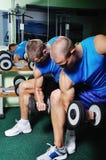 Μυϊκά άτομα που ασκούν σε μια γυμναστική Στοκ Εικόνες