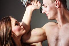 Μυϊκά άτομο και κορίτσι ζεύγους που θαυμάζουν τη δύναμή του Στοκ Φωτογραφίες