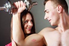 Μυϊκά άτομο και κορίτσι ζεύγους που θαυμάζουν τη δύναμή του Στοκ φωτογραφία με δικαίωμα ελεύθερης χρήσης