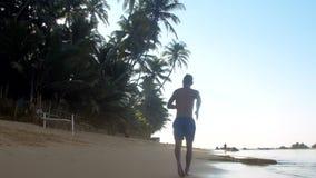 Μυϊκά gymnast τρεξίματα στην υγρή άμμο κοντά στον ατελείωτο ωκεανό φιλμ μικρού μήκους