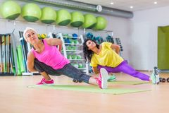 Μυϊκές θηλυκές γυναίκες ικανότητας που κάνουν την τεντώνοντας άσκηση στο εσωτερικό στην αθλητική λέσχη Στοκ Εικόνα