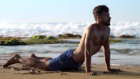 Μυϊκές gymnast στάσεις στη θέση γιόγκας στην αμμώδη παραλία φιλμ μικρού μήκους