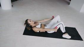 Μυϊκή γυναίκα άσπρο sportswear που επιλύει στη γυμναστική τα βάρη ανύψωσης Αθλητικό ξανθό κορίτσι που λικνίζει τον Τύπο στο εσωτε απόθεμα βίντεο