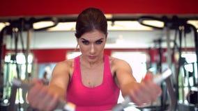 Μυϊκή γυναίκα αθλητών σε μια ρόδινη κορυφή που επιλύει στη γυμναστική τα βάρη ανύψωσης κορίτσι ικανότητας που ασκεί στη γυμναστικ απόθεμα βίντεο