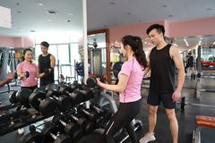 Μυϊκή γυναίκα που επιλύει στη γυμναστική που κάνει τις ασκήσεις με τους αλτήρες στους δικέφαλους μυς, ισχυρά αρσενικά γυμνά ABS κ Στοκ Εικόνες