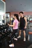 Μυϊκή γυναίκα που επιλύει στη γυμναστική που κάνει τις ασκήσεις με τους αλτήρες στους δικέφαλους μυς, ισχυρά αρσενικά γυμνά ABS κ Στοκ φωτογραφίες με δικαίωμα ελεύθερης χρήσης