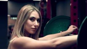 Μυϊκή γυναίκα που επιλύει στη γυμναστική τα βάρη ανύψωσης φιλμ μικρού μήκους