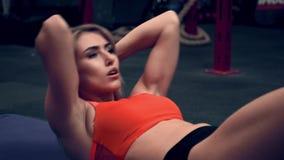 Μυϊκή γυναίκα που επιλύει στη γυμναστική τα βάρη ανύψωσης απόθεμα βίντεο