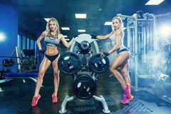 Μυϊκή προκλητική χαλάρωση γυναικών γυναικών ικανότητας δύο στη γυμναστική concept healthy lifestyle Bodybuilder στη γυμναστική Στοκ Φωτογραφία