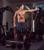 Μυϊκός αθλητής γυμνοστήθων που κάνει την άσκηση με έναν αποσυμπιεστή στη γυμναστική Στοκ φωτογραφίες με δικαίωμα ελεύθερης χρήσης
