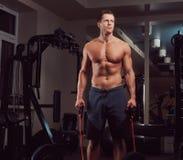 Μυϊκός αθλητής γυμνοστήθων που κάνει την άσκηση με έναν αποσυμπιεστή στη γυμναστική Στοκ Φωτογραφία