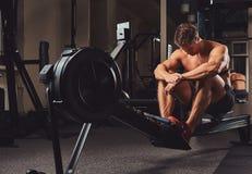 Μυϊκός αθλητής γυμνοστήθων που στηρίζεται μετά από ένα σκληρό workout ενώ κάθεται στη μηχανή κωπηλασίας στη γυμναστική Στοκ φωτογραφία με δικαίωμα ελεύθερης χρήσης