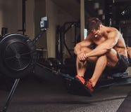 Μυϊκός αθλητής γυμνοστήθων που στηρίζεται μετά από ένα σκληρό workout ενώ κάθεται στη μηχανή κωπηλασίας στη γυμναστική Στοκ Φωτογραφίες