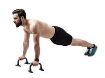 Μυϊκός αθλητής γυμνοστήθων που κάνει ώθηση-επάνω στην ώθηση επάνω στους φραγμούς Στοκ Φωτογραφία