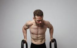 Μυϊκός αθλητής γυμνοστήθων που κάνει ώθηση-επάνω στην ώθηση επάνω στους φραγμούς Στοκ φωτογραφίες με δικαίωμα ελεύθερης χρήσης
