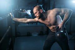 Μυϊκός αθλητής workout, άτομο που ανυψώνει kettlebell Στοκ εικόνες με δικαίωμα ελεύθερης χρήσης