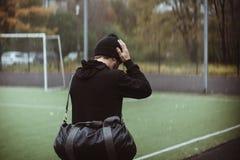 Μυϊκός αρσενικός αθλητής που παίρνει τη μόνιμη χαλάρωση σπασιμάτων μετά από να εκπαιδεύσει στοκ φωτογραφία με δικαίωμα ελεύθερης χρήσης