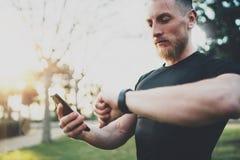 Μυϊκός γενειοφόρος αθλητής που ελέγχει τις μμένες θερμίδες στην εφαρμογή smartphone και το έξυπνο ρολόι μετά από την καλή σύνοδο  στοκ φωτογραφία με δικαίωμα ελεύθερης χρήσης