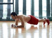 Μυϊκός και ισχυρός ασιατικός τύπος που κάνει την άσκηση σανίδων Στοκ Φωτογραφία