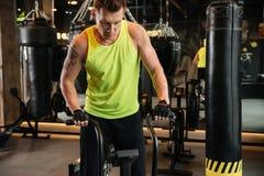 Μυϊκός νέος αθλητικός τύπος που χρησιμοποιεί τον εξοπλισμό γυμναστικής Στοκ Φωτογραφία