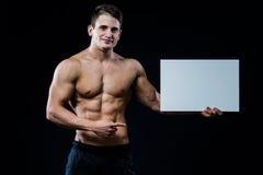 Μυϊκός νεαρός άνδρας γυμνοστήθων που στέκεται κρατώντας ένα κενό οριζόντιο άσπρο έμβλημα που δείχνει το δάχτυλο στο copyspace για Στοκ Εικόνες