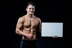 Μυϊκός νεαρός άνδρας γυμνοστήθων που στέκεται κρατώντας ένα κενό οριζόντιο άσπρο έμβλημα που δείχνει το δάχτυλο στο copyspace για Στοκ εικόνα με δικαίωμα ελεύθερης χρήσης
