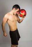 Μυϊκός νεαρός άνδρας με το μπαλόνι στοκ φωτογραφία