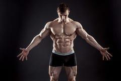 Μυϊκός τύπος bodybuilder που κάνει την τοποθέτηση πέρα από το μαύρο υπόβαθρο Στοκ φωτογραφίες με δικαίωμα ελεύθερης χρήσης